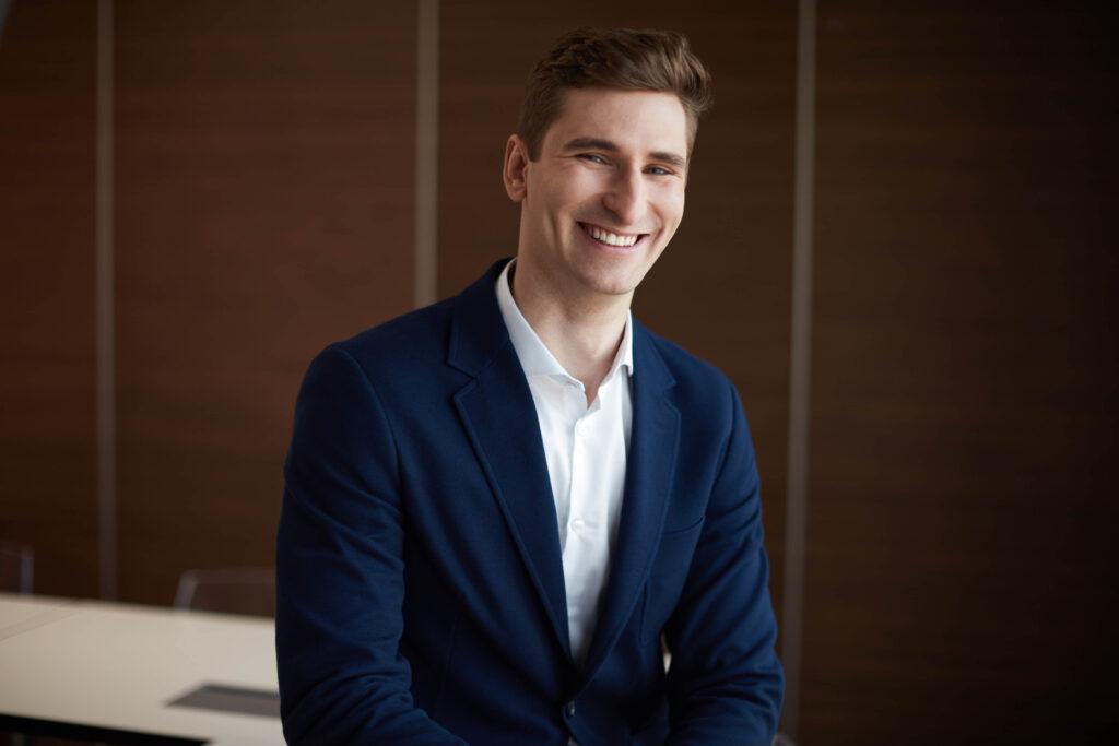 Uśmiechnięty młody mężczyzna w białej koszuli i marynarce