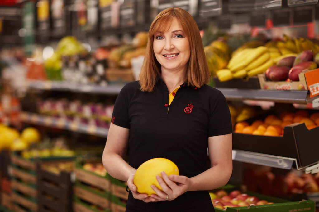 KObieta w czarnej koszulce polo trzymająca melona