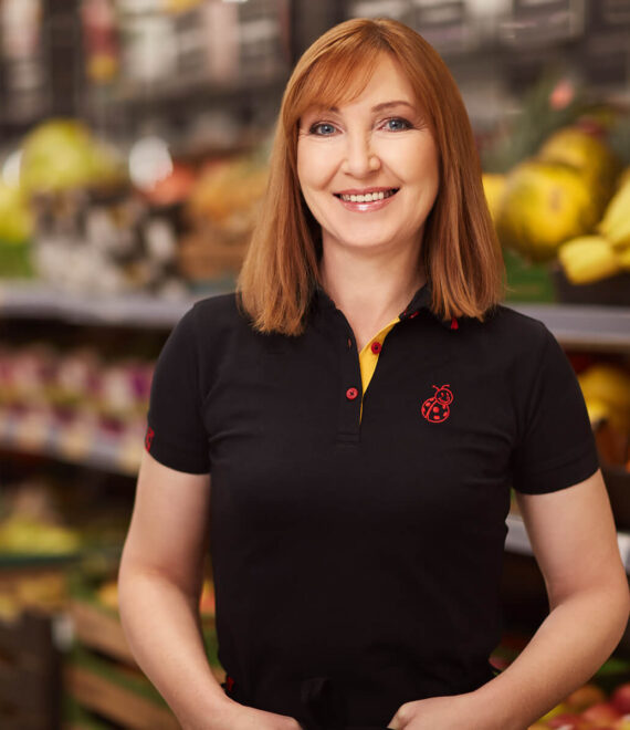 Uśmiechnięta kobieta w rudych włosach i czarnej koszulce polo na tle półek z warzywami