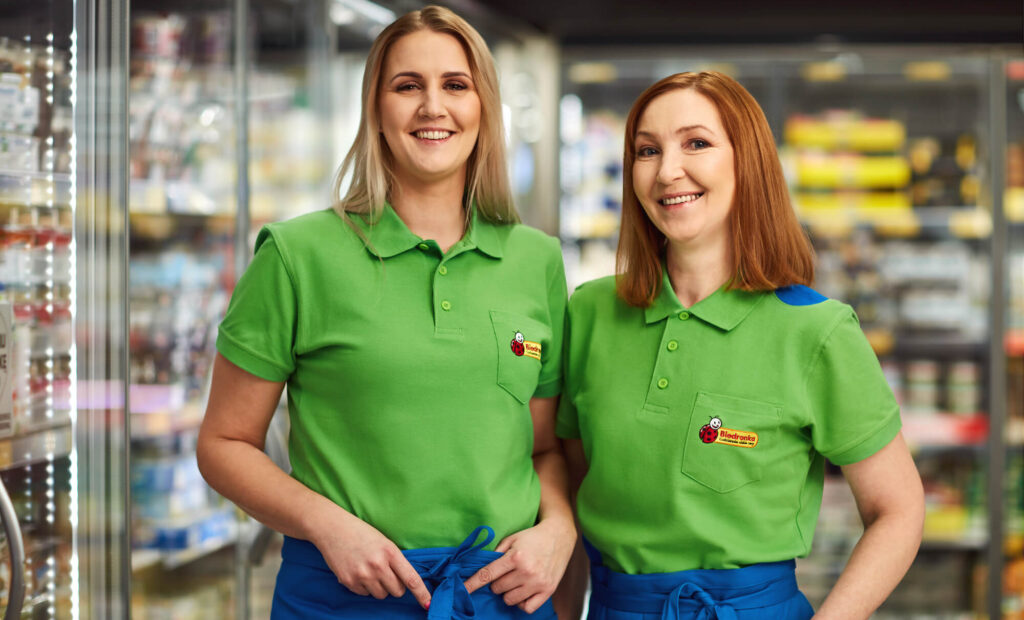 Dwie uśmiechnięte kobiety w zielonych koszulkach