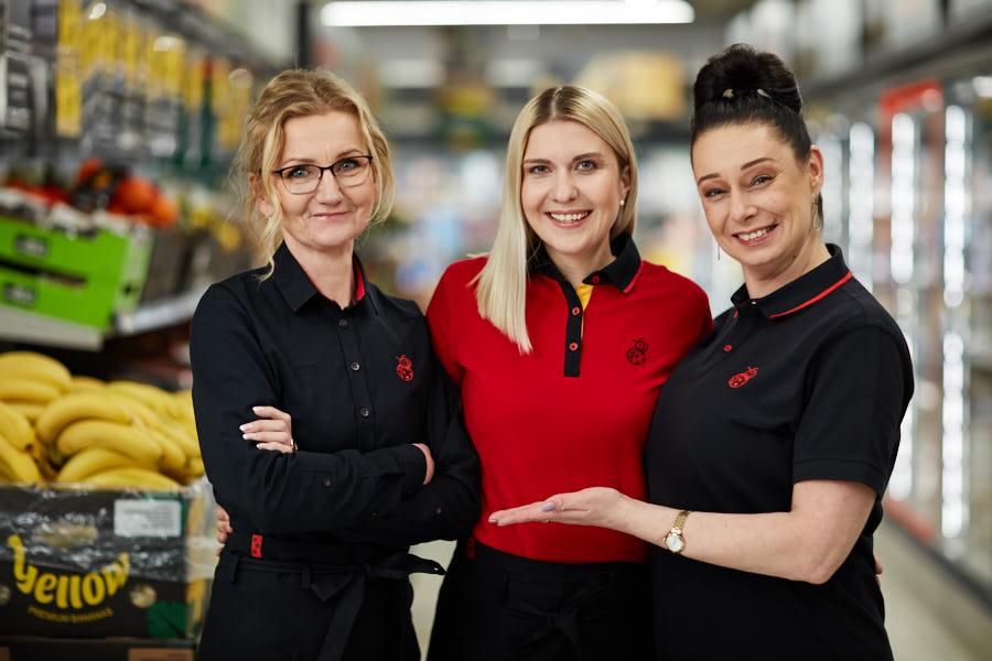 Trzy uśmiechnięte kobiety, jedna w czerwonej koszulce w środku, dwie w czarnych koszulkach