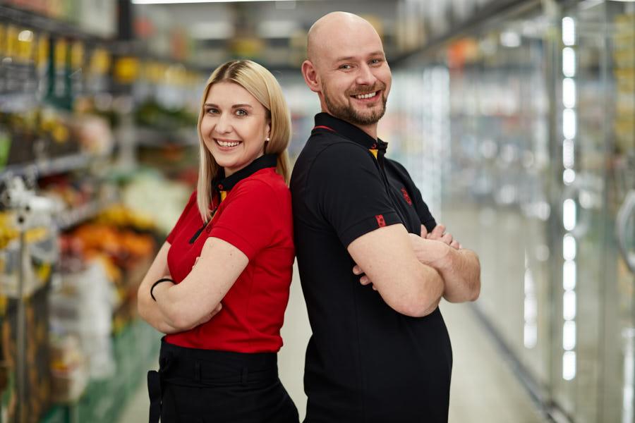 Uśmiechnięci kobieta w czerwonej koszulce i mężczyzna w czarnej koszulce opierający się plecami