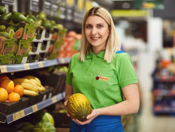 Młoda uśmiechnięta kobieta trzymająca owoc w ręce