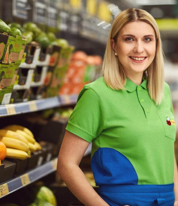 Młoda kobieta stojąca przy owocach w zielonej koszulce