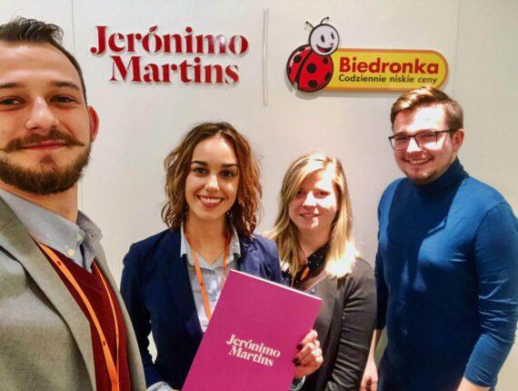 Grupa uśmiechniętych ludzi na tle logo Jeronimo Martins i Biedronki