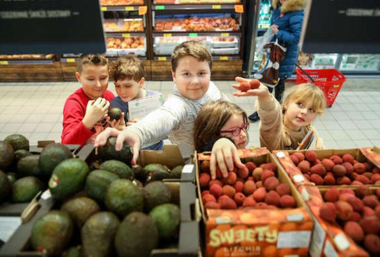 grupa dzieci przy skrzynkach z owocami