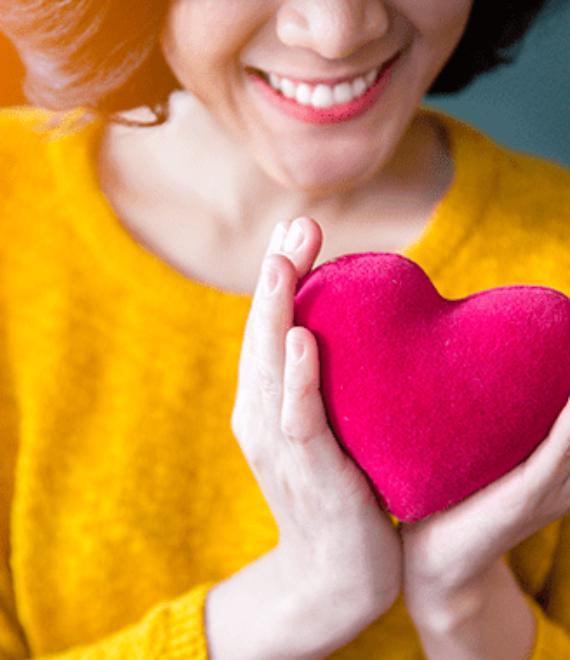 Kobieta w żółtym swetrze trzymająca pluszowe serce
