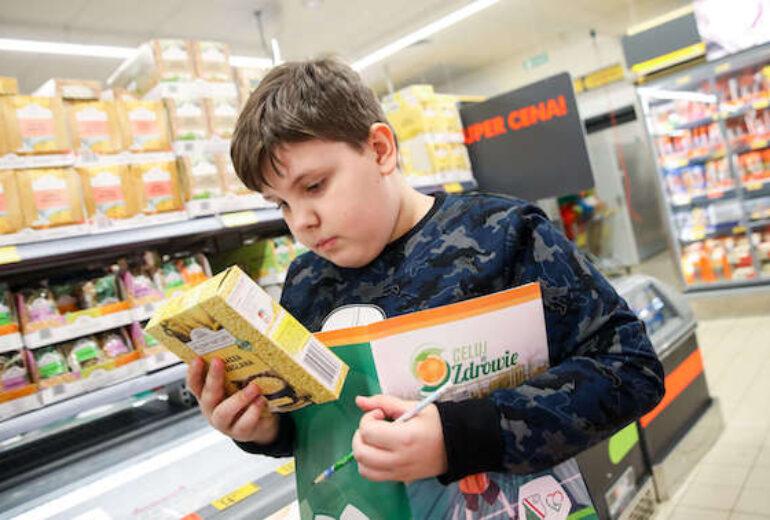 chłopiec czytający etykietę z opakowania kaszy