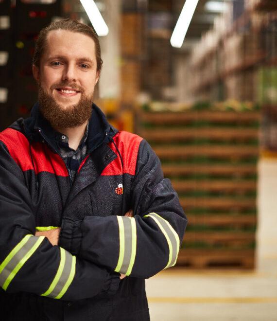Mężczyzna w uniformie roboczym stojący w magazynie