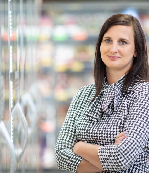 Kobieta w bluzce w kratkę stojąca przy lodówkach sklepowych