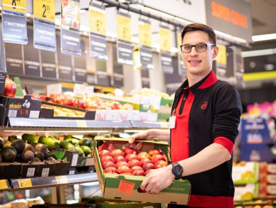 Zdjęcie młodego mężczyzny trzymającego skrzynkę z owocami