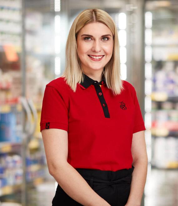 Kobieta w czerwonej koszulce stojąca na tle półek sklepowych