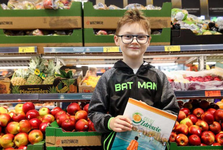 chłopiec w okularach przy skrzynkach z owocami