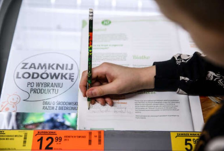 ręka dziecka trzymająca ołówek i robiąca notatki