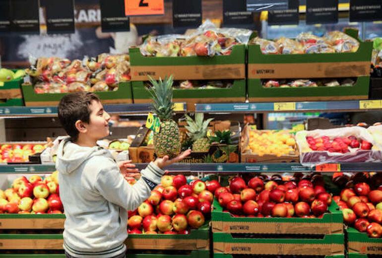 chłopiec w szarej bluzie przy skrzynkach z owocami