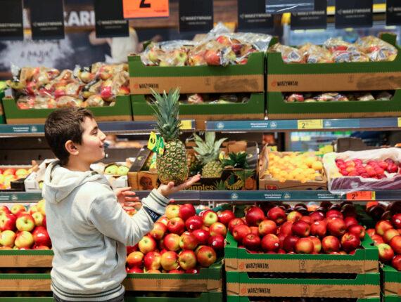 chłopiec w szarej bluzie przy regale z owocami