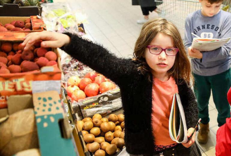 dziewczynka w okularach sięgająca po owoc