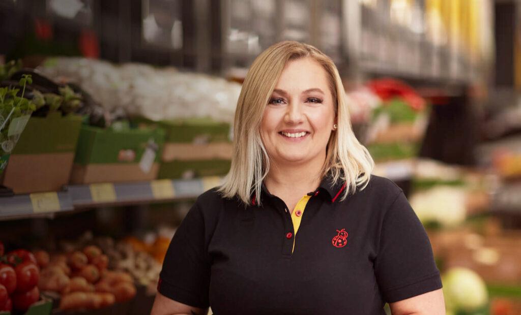 Uśmiechnięta kobieta w czarnej koszulce polo trzymająca pomidory