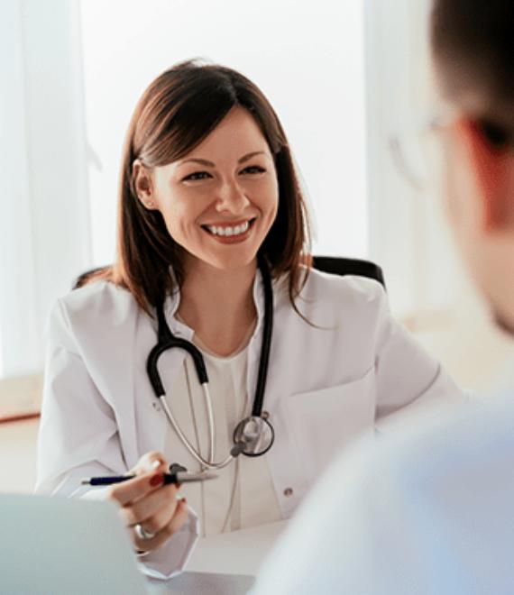 uśmiechnięta lekarka rozmawiająca z pacjentem