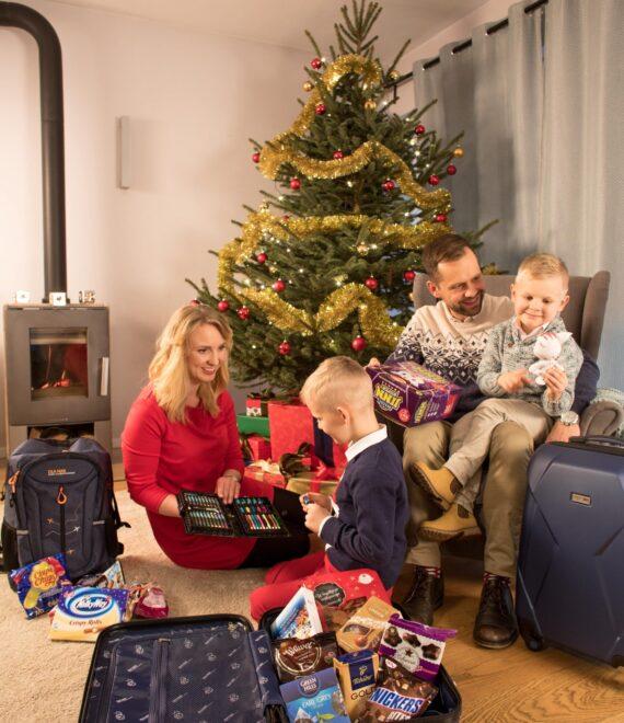 Rodzina rozpakowująca prezenty przy choince