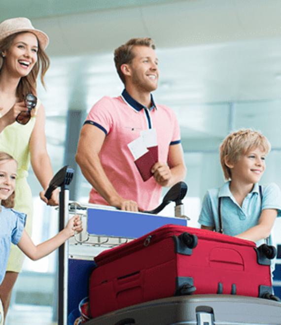 Rodzice z dwójką dzieci pchają walizki