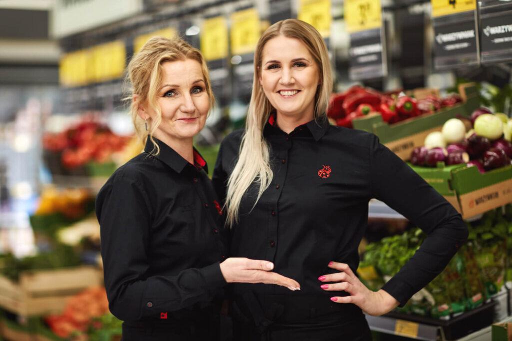 Dwie uśmiechnięte kobiety w czarnych koszulkach