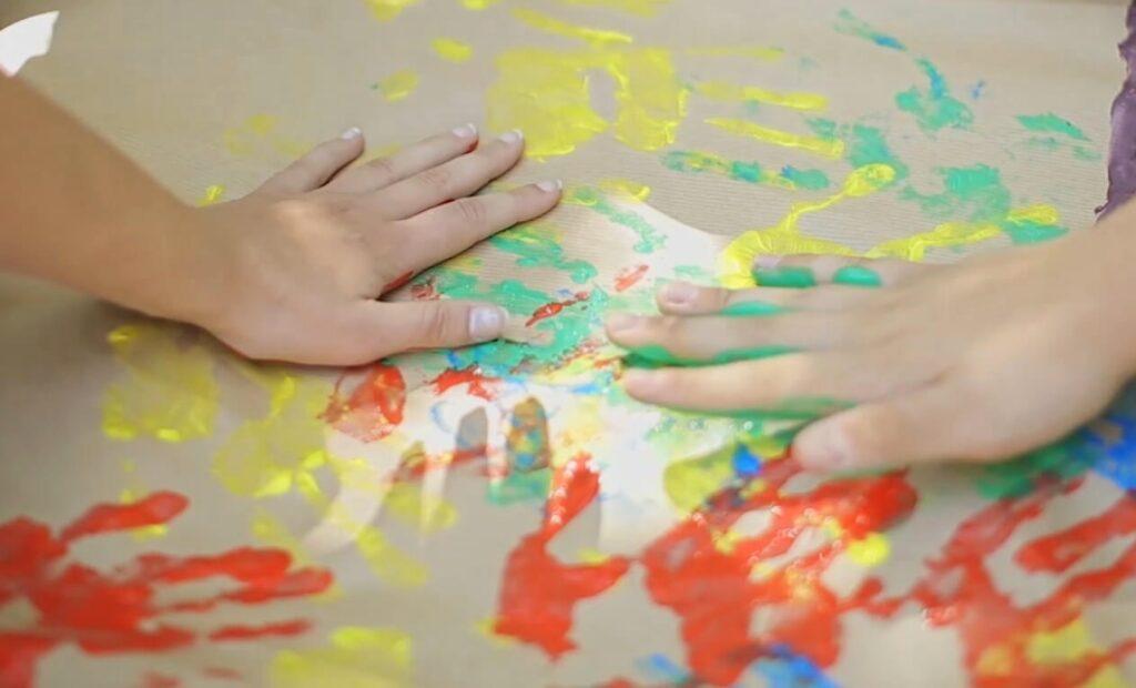 Dziecięce dłonie robiące kolorowe odciski