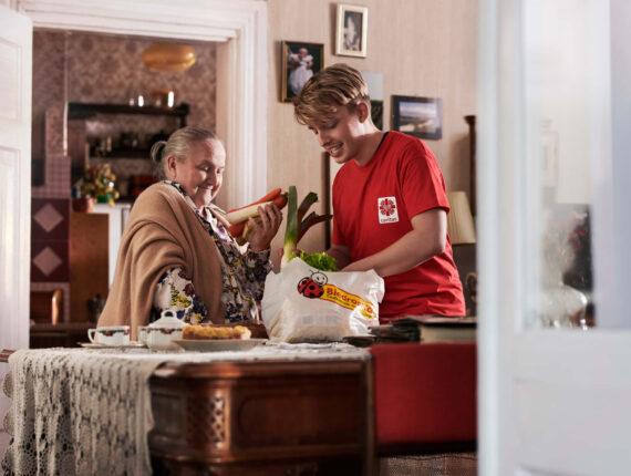 Młody chłopak i starsza kobieta rozpakowują zakupy