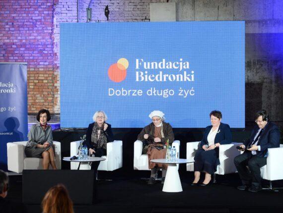 Pięć osób siedzących na tle telebimu z logo Fundacji Biedronki