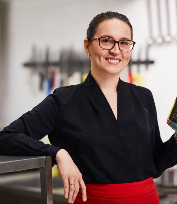 Młoda kobieta w okularach w czarnej koszuli trzymająca paczkę kawy
