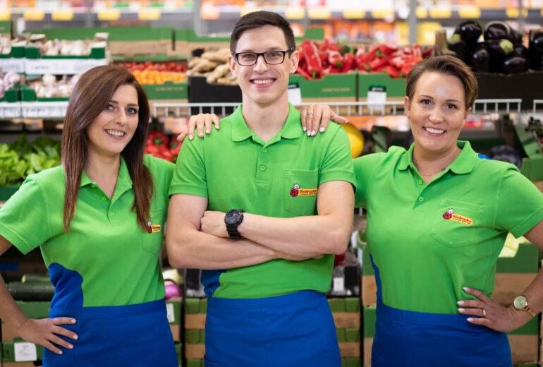 Troje pracowników Biedronki w zielonych koszulkach