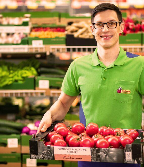 Mężczyzna trzymający skrzynkę z pomidorami