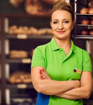 Kobieta w zielonej koszulce stojąca z założonymi rękami