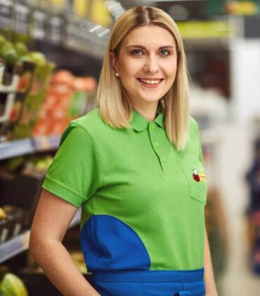 Молодий усміхається жінка в світле волосся в сорочці поло