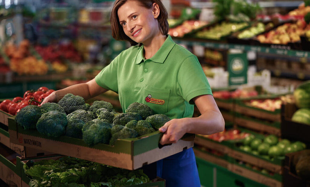 A young woman lifting a box of vegetables