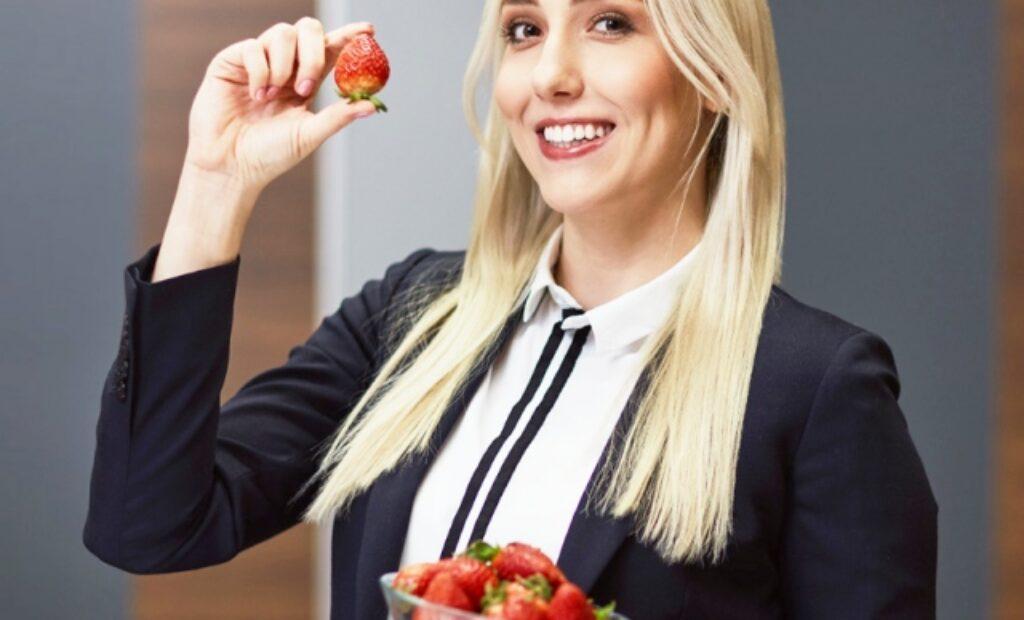 Młoda kobieta trzymająca truskawki