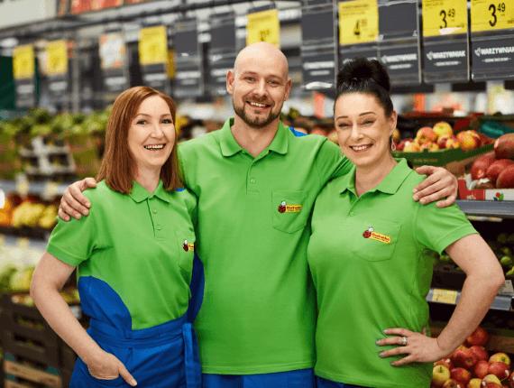 trzy osoby stojące w sklepie przy stoisku z owocami