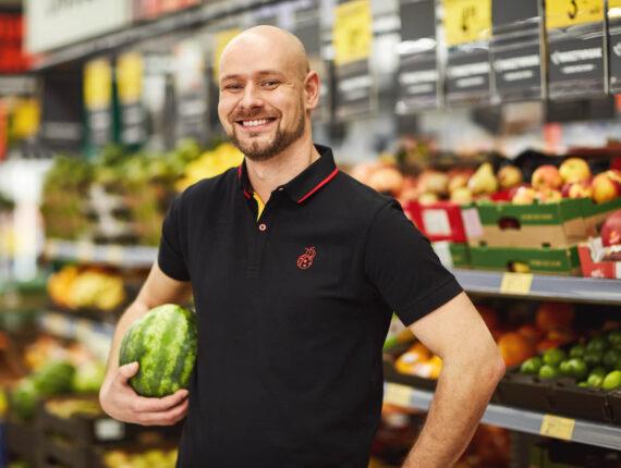 Uśmiechnięty mężczyzna w czarnej koszulce z arbuzem pod pachą