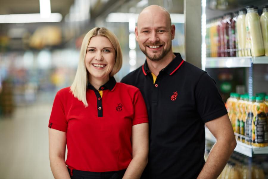 Młody mężczyzna w czarnej koszulce stojący obok uśmiechniętej kobiety w czerwonej koszulce
