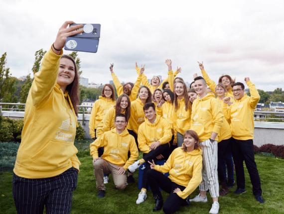 mlodzi ludzie w żółtych bluzach robiący sobie selfie
