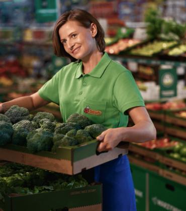 Kierownik Sklepu trzymający warzywa