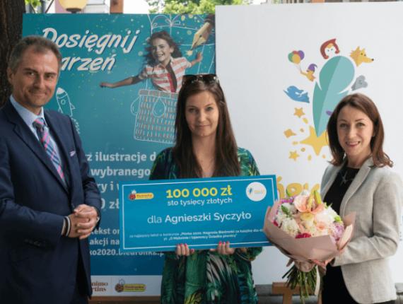 trzy osoby trzymające duży czek wystawiony na 100 tysięcy złotych