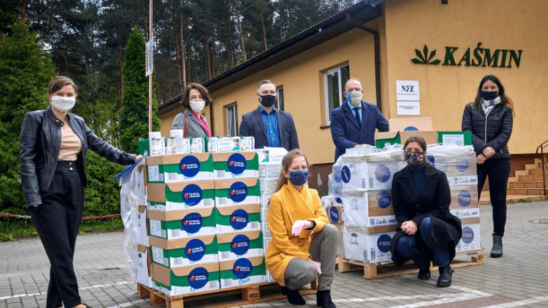 osoby w maseczkach stojące przy plateach z produktami
