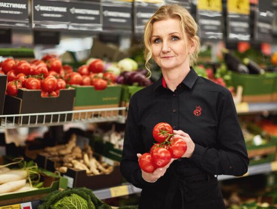 Kobieta w czarnej koszulce trzymająca pomidory