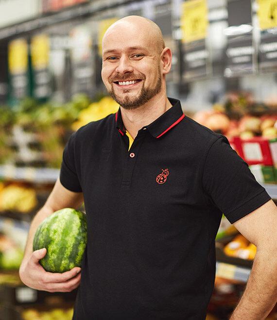 Uśmiechnięty młody mężczyzna w czarnej koszulce z arbuzem pod pachą