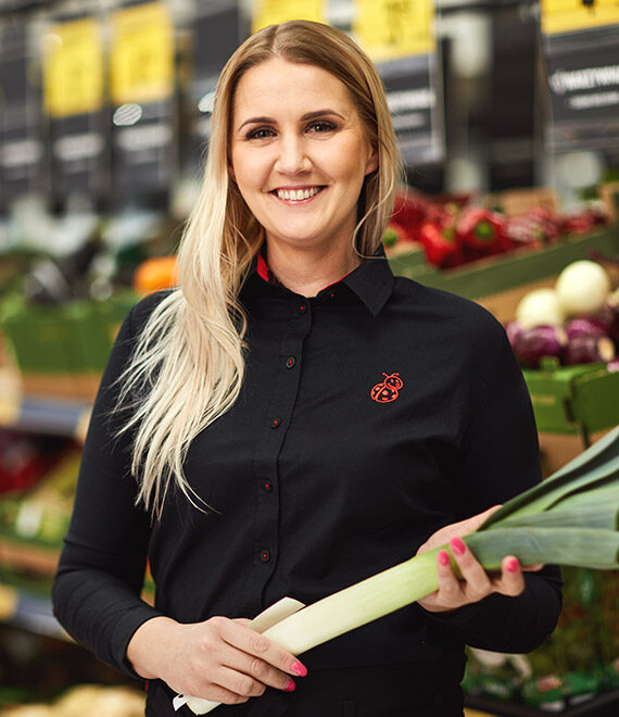 Młoda uśmiechnięta kobieta w czarnej koszulce trzymająca por w ręce