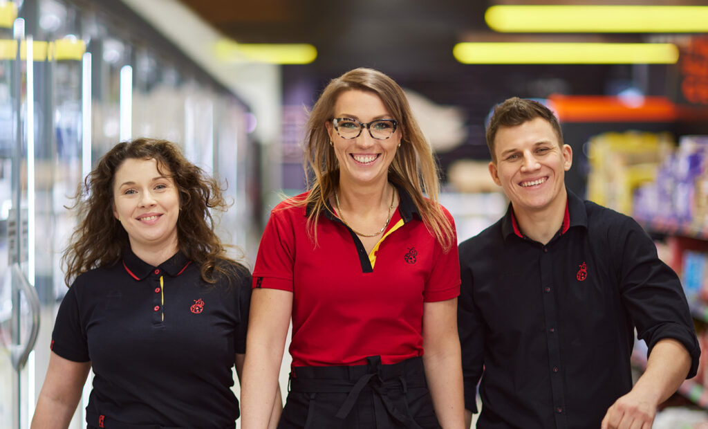 Troje uśmiechniętych pracowników Biedronki