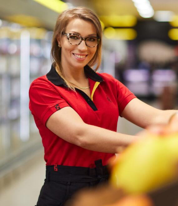 młoda kobieta układająca owoce i warzywa