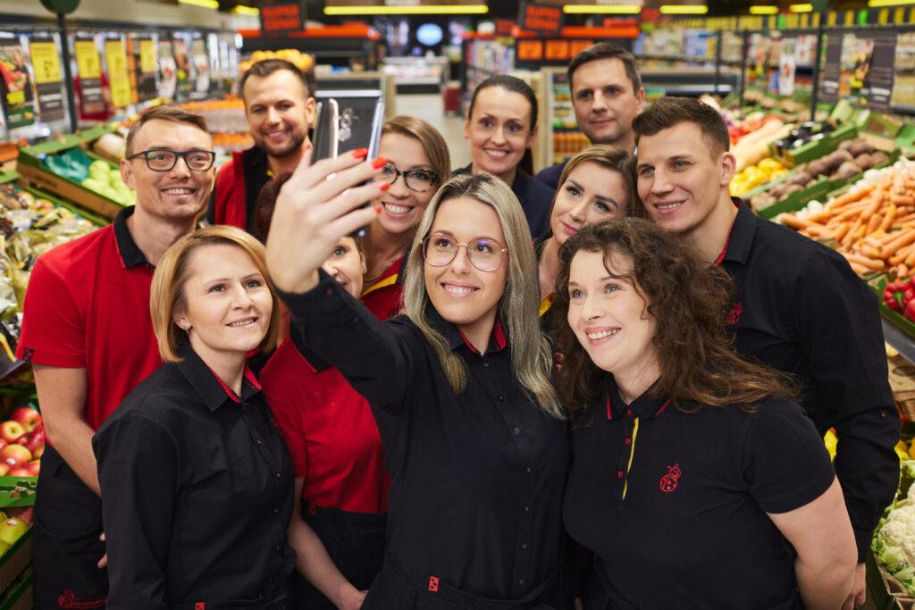 grupa pracowników biedronki robiących sobie zdjęcie