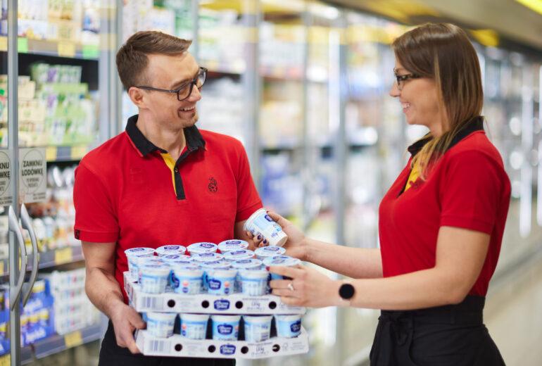 kobieta sięgająca po jogurt z kartonu